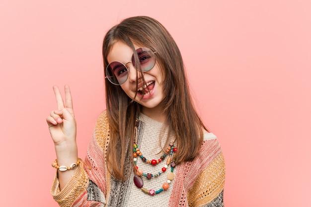 Menina hippie alegre e despreocupada, mostrando um símbolo de paz com os dedos.