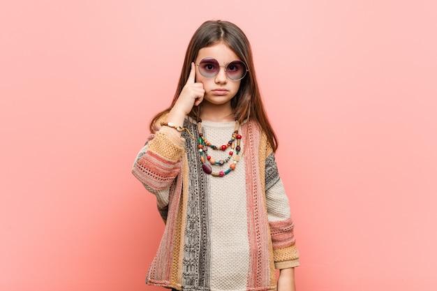 Menina hippie apontando o templo com o dedo, pensando, focado em uma tarefa