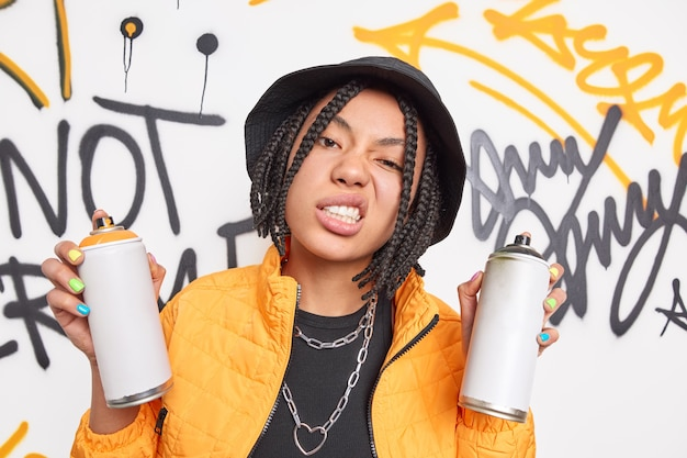 Menina hippie atrevida com dreadlocks aperta os dentes sorri afetado rosto segura dois sprays de aerossol usa roupas da moda desenha parede de graffiti tem estilo de vida de rua manicure colorida pertence à subcultura jovem