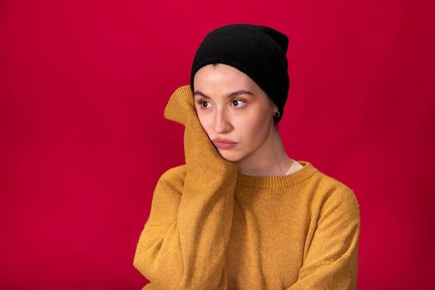 Menina hippie com boné preto e suéter mostarda pensando Foto Premium