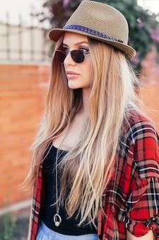 Menina hippie com chapéu retrô e óculos escuros se passando perto da parede do grunge. tem cabelo loiro comprido e liso e camisa vermelha.