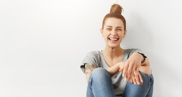 Menina hippie com coque de cabelo usando roupas elegantes, sentada no chão contra a parede branca do estúdio