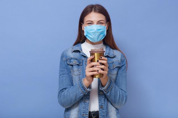 Menina hippie em máscara médica e jaqueta jeans, bebendo café de caneca térmica