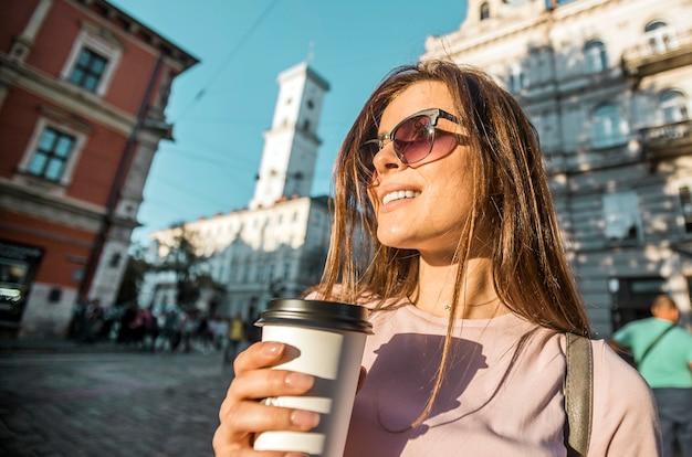 Menina hippie em óculos de sol, segurando a xícara de café