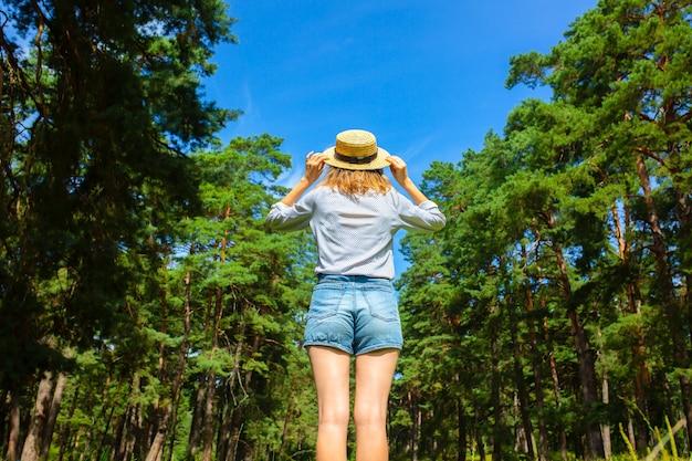 Menina hippie em pé de chapéu de palha na floresta. conceito de wanderlust. ideias para viagens. mulher bonita na natureza. ritmo de verão.
