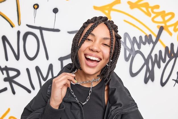 Menina hippie étnica positiva com um sorriso amplo segurando uma corrente de metal aproveitando o tempo livre e modelos de passatempo sobre uma parede de grafite criativa