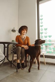 Menina hippie positiva sentada à mesa em um café bem iluminado, bebendo café e brincando com o cachorro