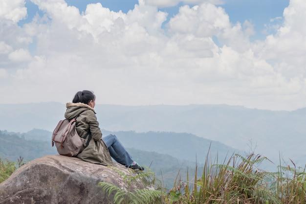 Menina hippie, sentado no rochoso da montanha