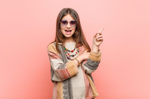 Menina hippie sorrindo alegremente apontando com o dedo indicador fora.