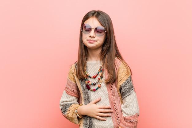 Menina hippie toca barriga, sorri suavemente, comendo e conceito de satisfação.