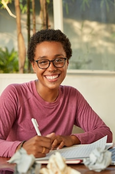 Menina hipster positiva com cabelo curto encaracolado, sorri amplamente, usa piercing, escreve a ideia criativa no bloco de notas, envolvida no processo de trabalho, rodeada de bolas de papel, senta-se no local de trabalho sozinha