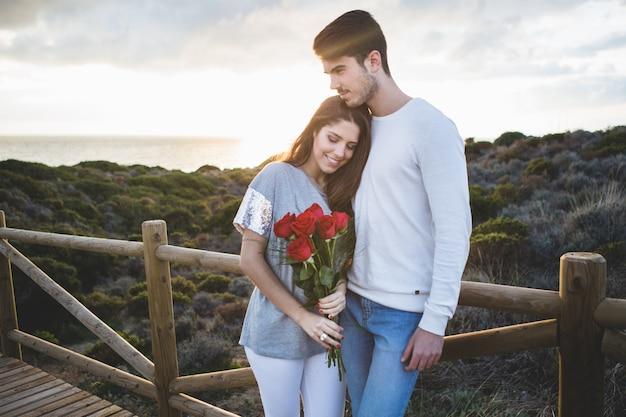 Menina inclinada sobre seu namorado, segurando um buquê de rosas