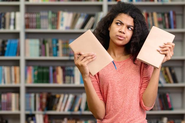 Menina indecisa em escolher um livro para ler