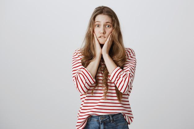 Menina indecisa preocupada mordendo o lábio e parecendo ansiosa