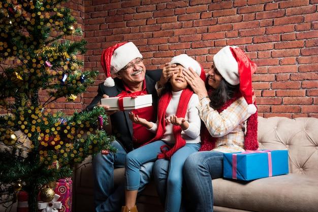Menina indiana asiática fofa celebrando o natal com os avós e a árvore de natal, sentada no sofá, usando chapéu de papai noel e muitos presentes