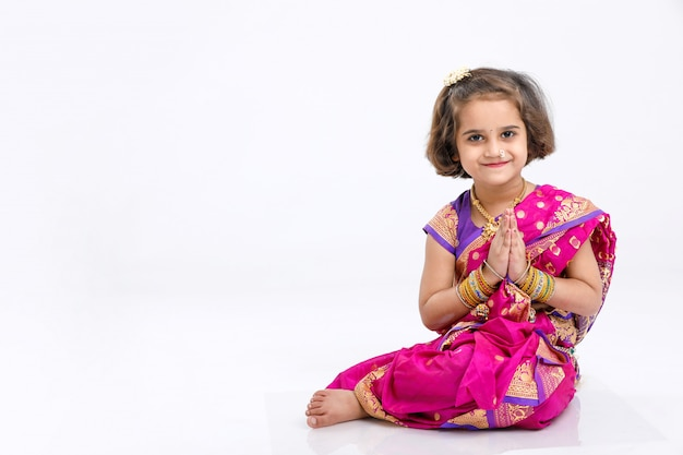 Menina indiana / asiática pequena bonito em rezar pose e sentado