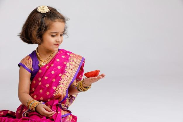 Menina indiana / asiática pequena bonito no desgaste tradicional que guarda uma lâmpada de óleo do diya ou da terracota no festival de diwali.