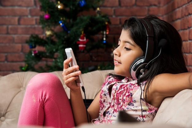Menina indiana asiática pequena fofa ouvindo música usando fones de ouvido ou fone de ouvido no smartphone, sentada no sofá ou sofá em casa