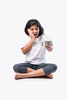 Menina indiana asiática segurando um modelo de casa de papel contra um fundo branco - conceito de casa e família