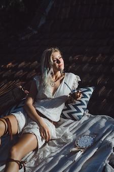 Menina indiana bonita da hippie com cabelo louro longo no telhado que bebe o chá do companheiro.