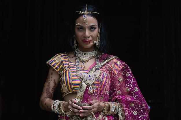 Menina indiana bonita no vestido nacional em um fundo preto