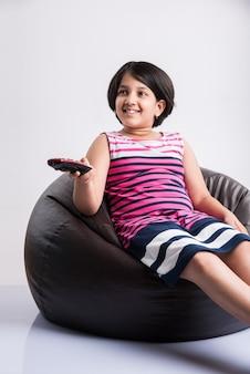 Menina indiana bonitinha assistindo televisão ou tv enquanto muda de canal usando o controle remoto, sentada sobre o saco de feijão, isolado sobre um fundo branco