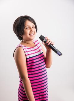 Menina indiana bonitinha cantando no microfone, isolada sobre um fundo branco