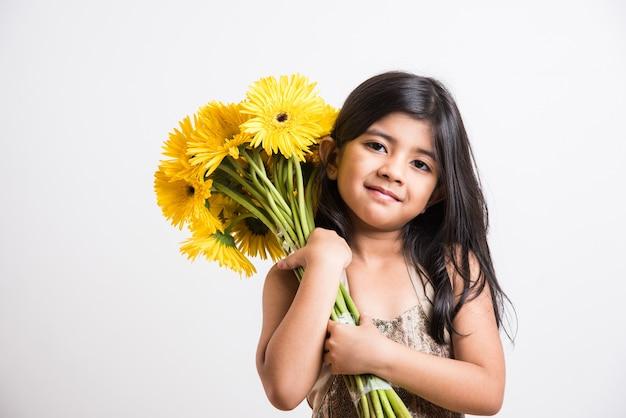Menina indiana bonitinha segurando um ramo ou buquê de flores frescas gerbera amarela. isolado sobre fundo branco