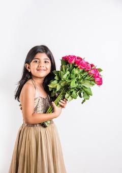 Menina indiana bonitinha segurando um ramo ou buquê de rosas vermelhas frescas ou flores de gulab. isolado sobre fundo branco