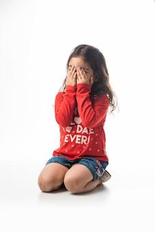 Menina indiana brincando de esconde-esconde enquanto está sentada, isolada no fundo branco