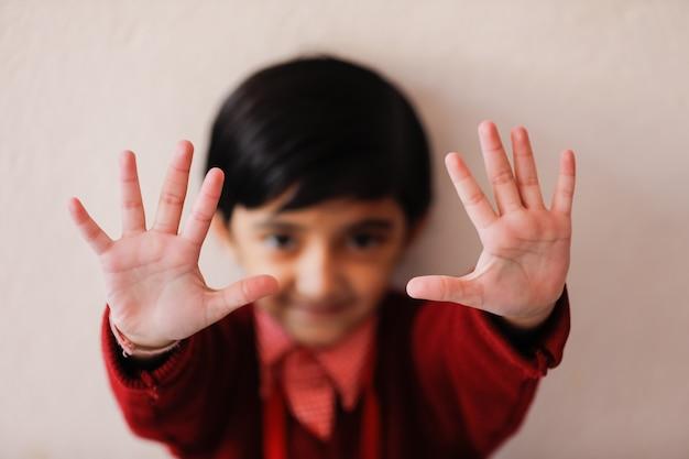 Menina indiana em uniforme escolar e mostrando expressão