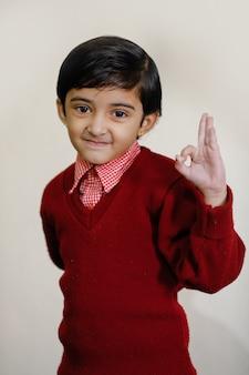 Menina indiana em uniforme escolar e mostrando o dedo