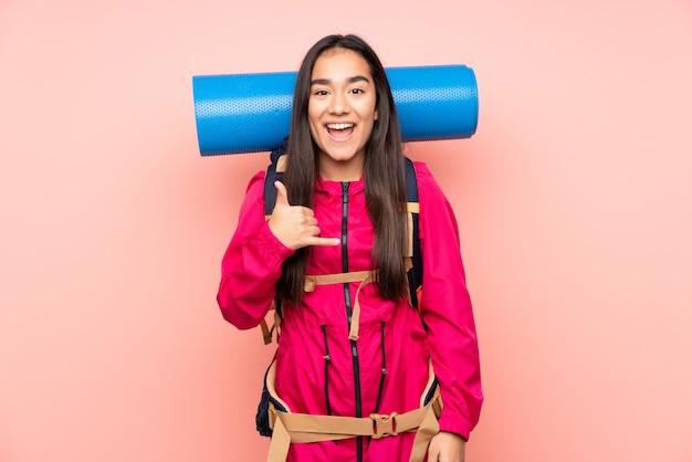 Menina indiana jovem alpinista com uma mochila grande na parede rosa, fazendo gesto de telefone