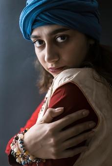 Menina indiana no turbante em um fundo preto.