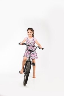 Menina indiana ou asiática bonitinha andando de bicicleta, isolada sobre um fundo branco segurando balões