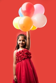 Menina indiana ou asiática bonitinha com balões coloridos ou gubbare em hindi, sobre fundo branco ou vermelho