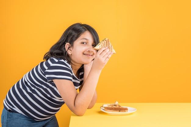 Menina indiana ou asiática bonitinha comendo hambúrguer saboroso, sanduíche ou pizza em um prato ou caixa. permanente isolado sobre fundo azul ou amarelo.