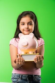 Menina indiana ou asiática bonitinha segurando o cofrinho rosa e os livros em pé, isolada sobre um fundo verde