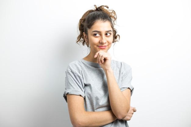Menina indiana pensativa em um fundo branco. pensando na ideia de uma jovem sorridente