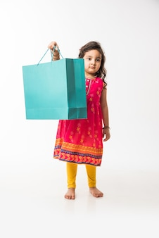 Menina indiana segurando sacolas de compras, isolada sobre um fundo branco
