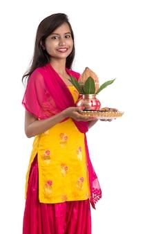 Menina indiana segurando uma kalash de cobre tradicional com pooja thali, festival indiano