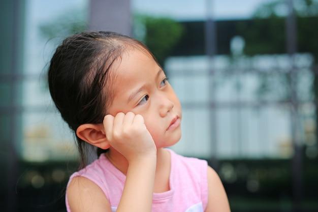 Menina infeliz da criança pequena com postura sua mão no mordente.