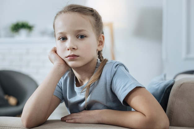 Menina infeliz de cabelos louros e olhos azuis pensando e segurando a cabeça com a mão enquanto está sentada no sofá