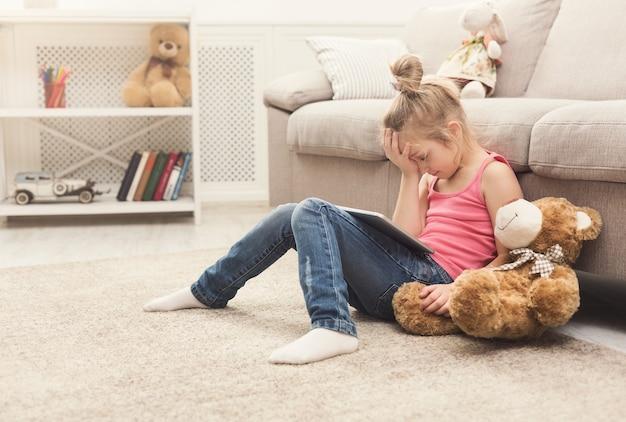 Menina infeliz jogando jogos online no tablet digital. criança do sexo feminino triste sentada no chão perto do sofá com seu ursinho de pelúcia. conteúdo chocante e conceito de rede social
