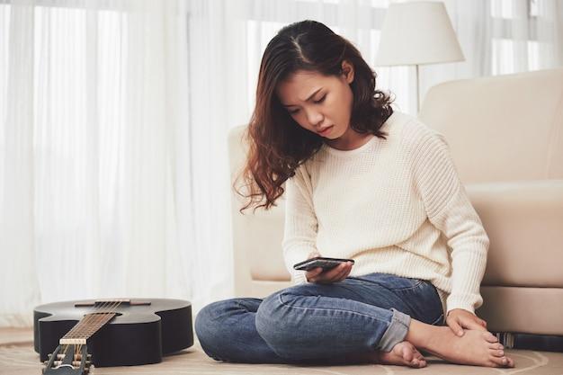 Menina infeliz lendo a mensagem de texto