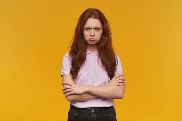 Menina infeliz, mulher ruiva chateada com cabelo comprido. vestindo uma camiseta rosa. conceito de pessoas e emoção. faz beicinho e mantém os braços cruzados. isolado sobre a parede laranja