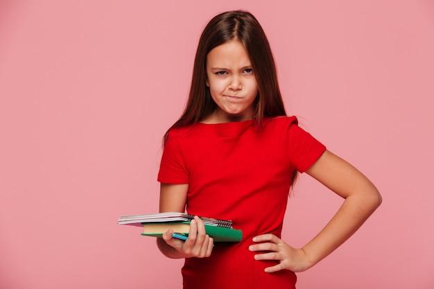 Menina infeliz no vestido vermelho, segurando o livro e olhando