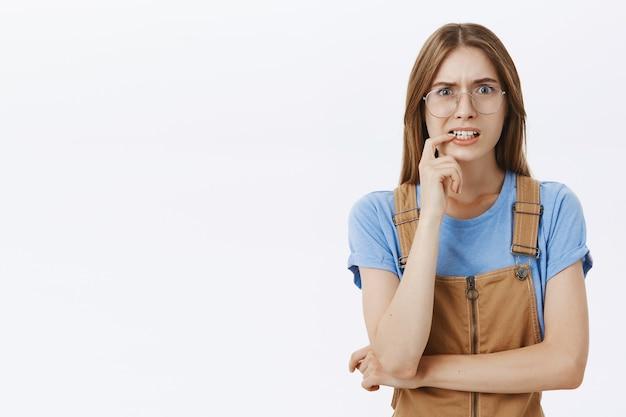Menina insegura e preocupada de óculos, mordendo o dedo, parecendo ansiosa ou assustada