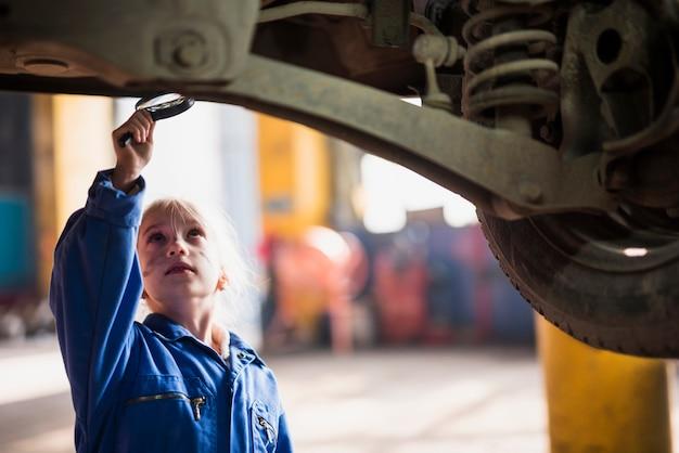 Menina inspecionando o carro com lupa