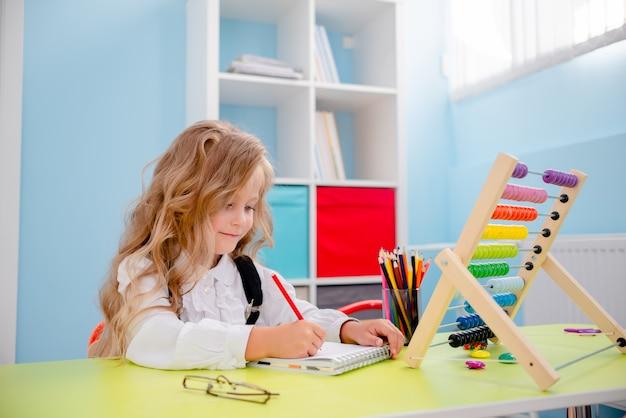 Menina inspirada na mesa com giz de cera. mesa de escola com material escolar, lápis, bolsas, caderno de desenho e ábaco. menina loura pequena que veste vidros de volta ao conceito da escola.